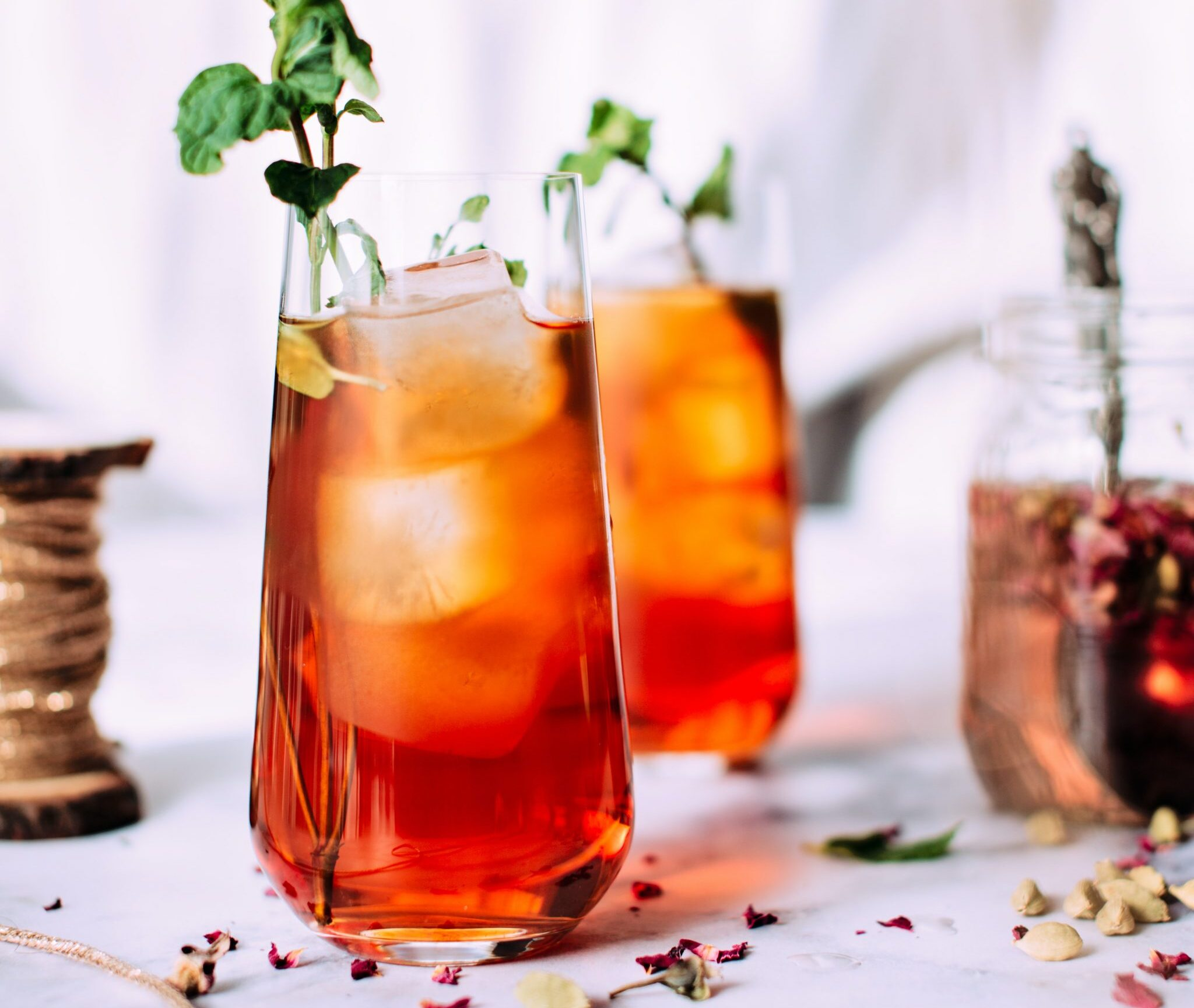 Iced Tea that is styled with a sprig of a green herb. There are roses in the background.