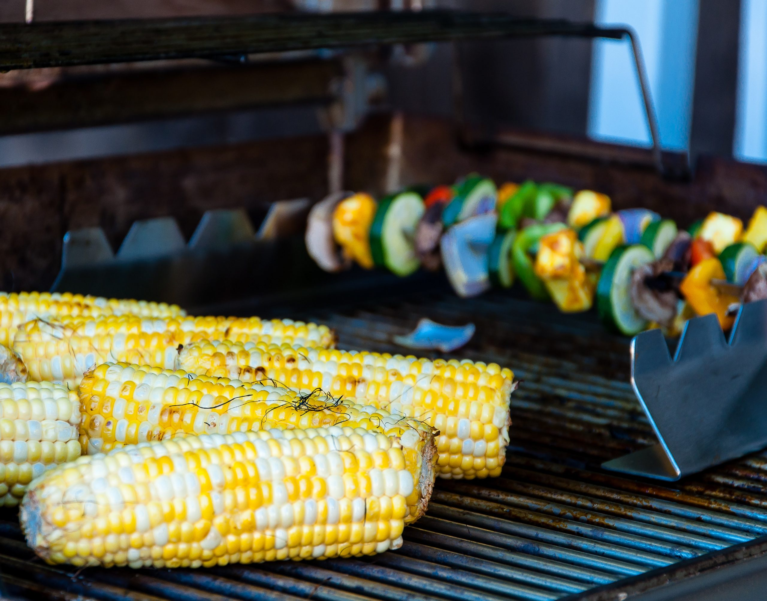 yellow corn and veggies on a grill